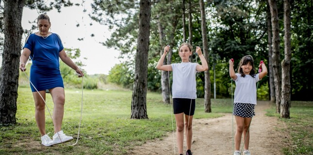 School children in white t shirts skipping ropes at public park